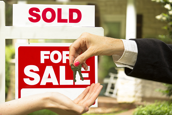 """Real estate agent gives house keys to new buyer in front of a red and white """"Sold, Home for Sale"""" sign. Stone, wood house that is for sale and has just been sold. Green grass and bushes indicate the spring or summer season. Front porch and windows in background. Residential neighborhood.  Moving house, relocation concepts. Unrecognizable people."""